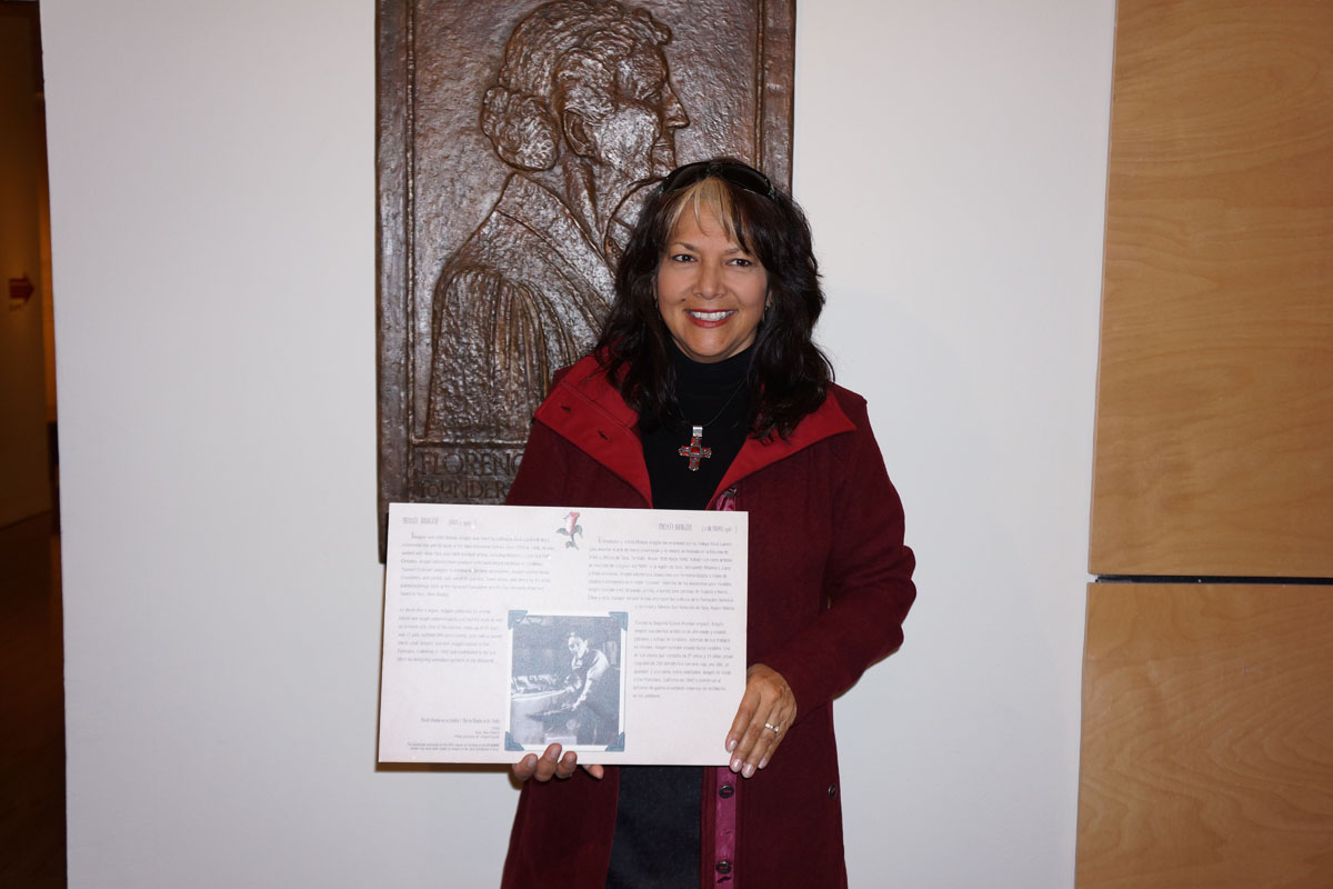 Debbie Brehm, granddaughter of woodcarver Moisés Aragón, with a text panel that honored Aragón in a 1999 museum exhibition